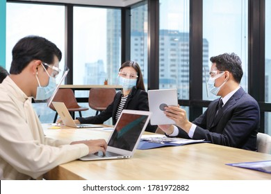 Asian people working together in co-working space following social distancing and new normal policy by wearing facial mask in the business office workplace during covid-19 outbreak(focus on right man)