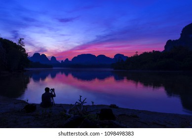 Asian photographer with digital camera photograph beautiful natural view of mountain and lake on twilight time before sunrise with reflexion on water.