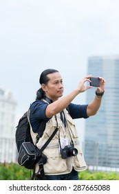 Asian photojournalist taking photo with a smartphone