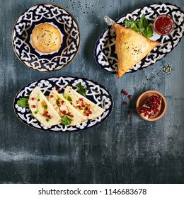 Asian Pies Collection with Qutab and Samosa on Dark Rustic Background Top View and Flat Lay. Gozleme with Cheese, Homemade Indian Samsa Stuffed with Beef and Onion and Traditional Uzbek Burekas