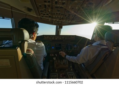 Asian pilots were operating the commercial airplane from taking off from airport in nice weather sunny day.
