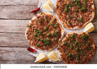 Asian pizza lahmacun on a wooden table. horizontal view from above