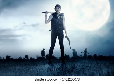 Asian policewoman with the gun and baseball bat in her hand face the zombies on the grass field at night. Halloween concept