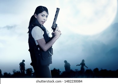 Asian policewoman with the gun on her hand face the zombies on the grass field at night. Halloween concept
