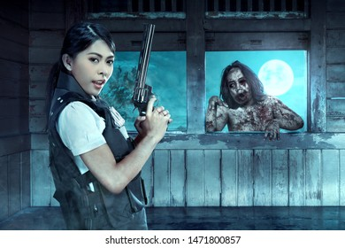 Asian policewoman with the gun on his hand face the zombies on the old wagon at night. Halloween concept