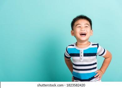 Asiatisches Portrait süßer kleiner Junge fröhlicher Gesicht, lächelt und schaut auf Kamera, Studioaufnahme einzeln auf blauem Hintergrund