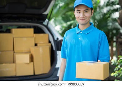 Asian Postman in blue uniform holding package. Delivery concept