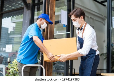 Asian Postman delivery in blue uniform send food ingredients box deliver to restaurant waiter in coffeehouse. Attractive barista worker wear mask due to Covid-19, sign for parcel and carry into cafe.