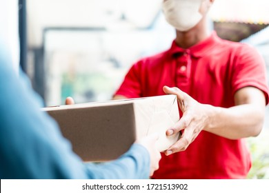 Asian postman, deliveryman wearing mask carry small box deliver to customer in front of door at home. Man wearing mask prevent covid19, corana virus affection outbreak. Home delivery shopping concept.