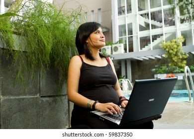 Asian pregnant business woman happy working with laptop