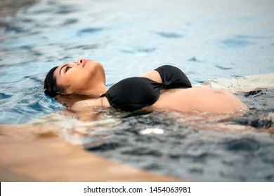 Asian pregnant woman with big belly. Relax and exercise and yoga at swimming pool, Water Yoga.