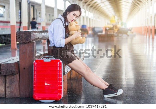 Asian pregnant woman traveler sitting on hugging Teddy Bear with a red suitcase at railway station travel.