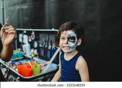 Asian preschooler doing skeleton face paint in the outdoor ready for carnival. Halloween party in outdoors. Long haired kid with blue shirt. Cheerful child ready for festival. Activity for children.