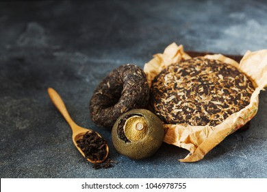 Asian pressed pu-erh tea and shu pu'er in tangerine on dark slate background copy space