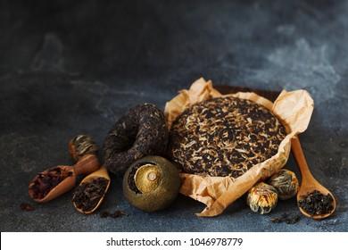 Asian pressed pu-erh tea, shu pu'er in tangerine, blooming tea in ball on dark slate background copy space