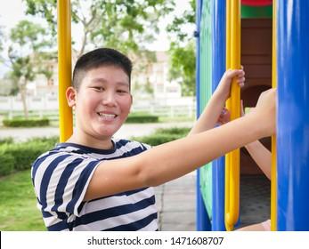 Asian preteen boy enjoy with outdoor playground.