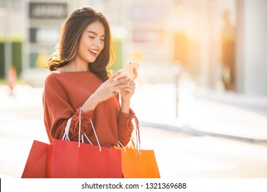 Asian pretty girl holding shopping bags while using smartphone background shopping mall concept.