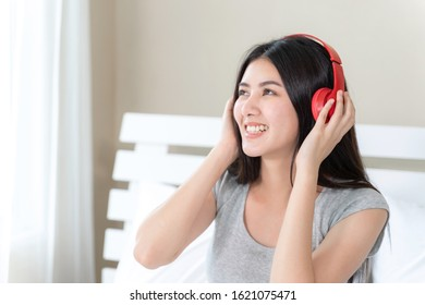 Asian pretty teenage woman wearing red bluetooth headphone, Dance and smiley for listening music with joyful, copy space