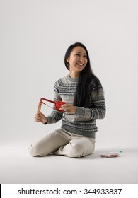 Asian pretty woman with Christmas Gift and Slingshot on Plain Background