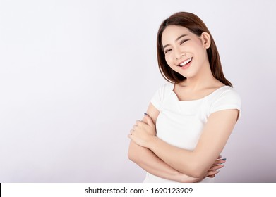 Asian pretty woman in white t-shirt and white pants pretending glad happy face with copy space on white background. Information telling, shopping promotion, announcement, selling support concept.