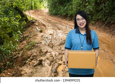 Asian pretty worker carrying box on mud road background, Asian delivery woman carrying boxes on mud road background