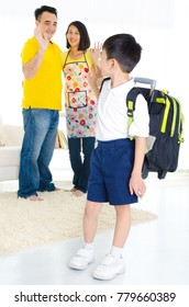Asian primary school student ready to school saying goodbye to his parent