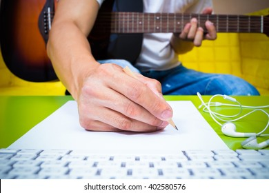 asian professional composer hands writing songs on white paper with acoustic guitar & computer