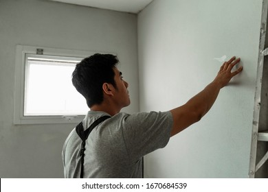 Asian professional handyman checking on the cement wall to see how strong is it. Smart asian handyman touching the wall.