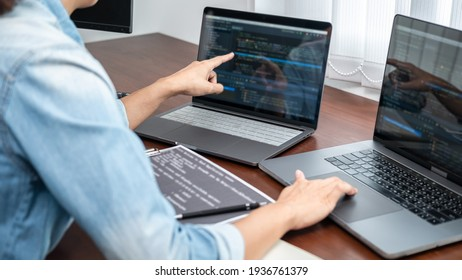 Asian programmer woman pointing and looking on multiple laptop screen to writing code and database while working about development website or applications in software development office