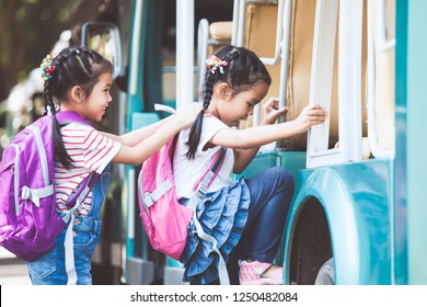 Asian pupil kids with backpack holding hand and going to school with school bus together. Back to school concept.