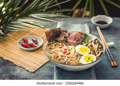 Asian ramen noodle in broth with meat and pickled egg in bowl on dark background.Ramen bowl.