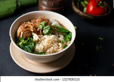 Asian ramen noodles soup and chicken in bowl on dark background.