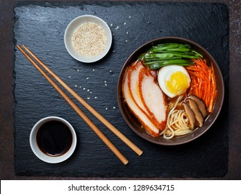 asian ramen soup with chicken, egg, carrots, green onions on a dark background. view from above