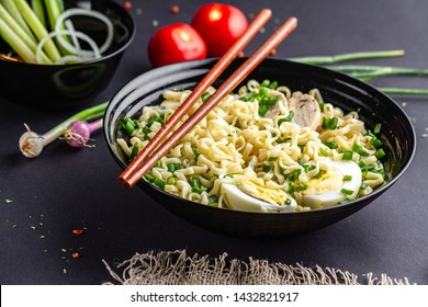 Asian ramen soup with chicken, egg, chives in black bowl on table. Ramen noodles bowl with vegetables