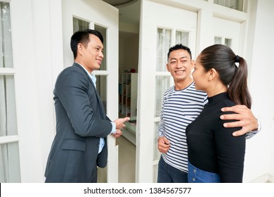 Asian real estate agent opening the door of the house and inviting young couple to come inside and seeing the house