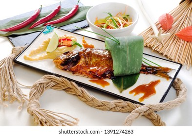 Asian recipe - Homemade grilled fish - healthy seafood concept. Fish on a white plate, tossed with sauce and lime, on a black plate in a light composition. Close up