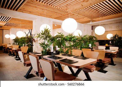 Asian restaurant interior with wooden ceiling and walls and green tall plants. Japanese style restaurant interior