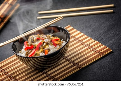 Asian rice with beef in black plate with chopsticks on dark stone table