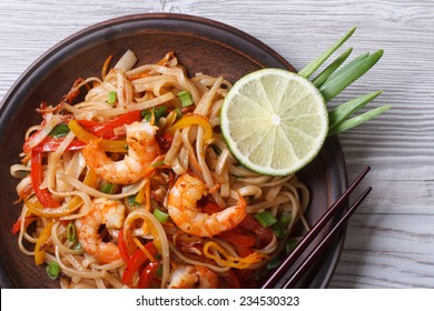 Asian rice noodles with shrimp and vegetables close-up on the table. top view of a horizontal