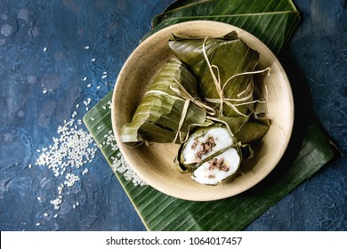 Asian rice piramidal steamed dumplings from rice tapioca flour with meat filling in banana leaves served in ceramic bowl with rice above over blue texture background. Top view, space.