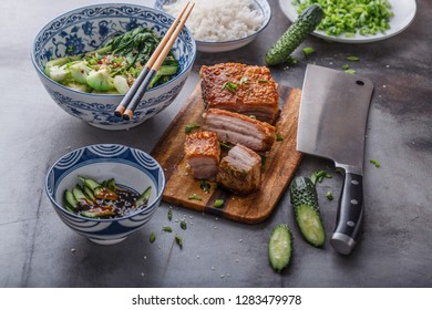 Asian roasted pork belly with crispy skin on concrete background.