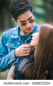 Asian romance couple eye contact and spending time together in the park, loving concept.