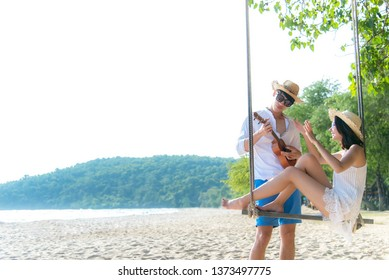 Asian romantic couple is sitting on sea beach on rope swing relax and happiness for holiday.  Honeymoon relax together on summer travel destination and crazy.  Valentine, Travel and Summer Concept.