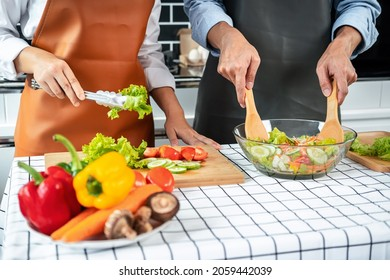 Asian romantic couple using tongs lettuce and tomato on wooden chopping board into bowl while young man holding ladle to mixing vegetable salad for cooking healthy meal in the kitchen at home