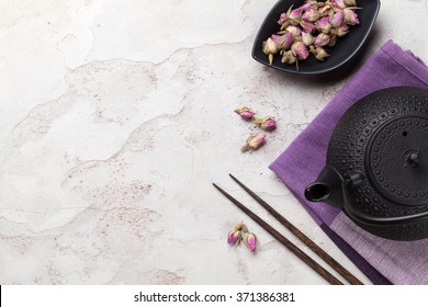 Asian rose tea and teapot over stone table. Top view with copy space
