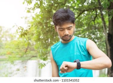 Asian runner athlete man looking at smartwatch heart rate monitor GPS smart watch. Runner man checking run performance for training running