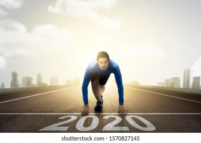 Asian runner man ready to run on the 2020 line. Happy New Year 2020