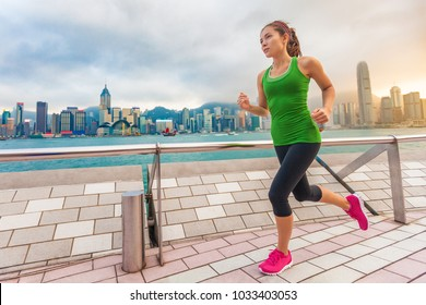 Asian runner woman on Hong Kong city run. Jogging at China travel sightseeing skyline. Healthy active lifestyle urban people training outdoors in summer sunset.