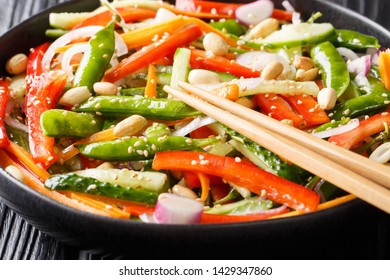 Asian salad of carrots, peas, peppers, cucumbers and onions close-up on a plate on the table. horizontal