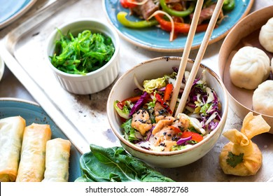 Asian salad with chicken stir-fry, bok choy, cabbage and pepper, dim sum bowl, spring rolls, seaweed and beef salad with vegetables. Chinese style dinner. From above. Pan-asian food. Selective focus